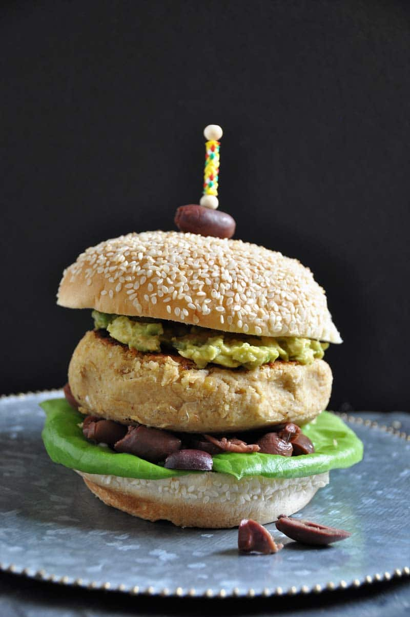 Hummus burger on a silver plate with an olive stuck on the top of a sesame seed bun with a toothpick
