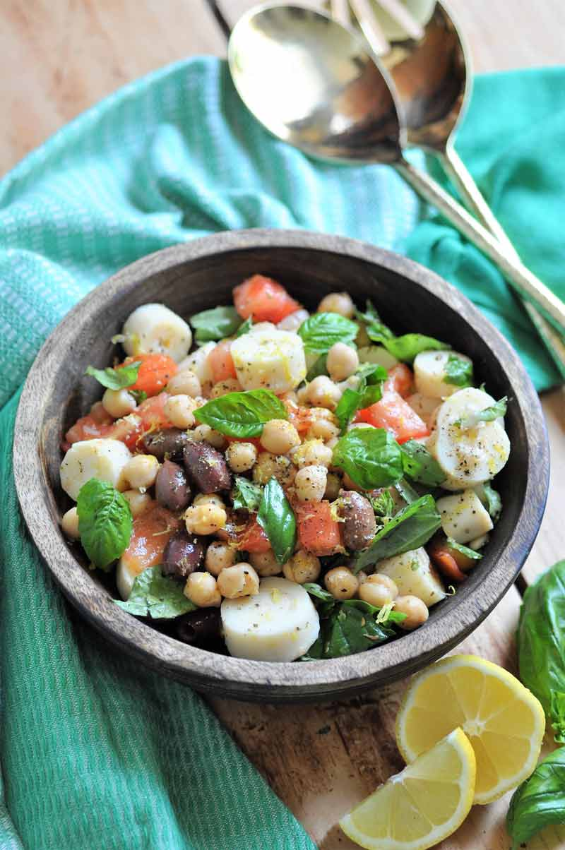 Chickpea salad with vegetables in a wood bowl with a green napkin around it and gold serving utensils and lemon wedges on the side