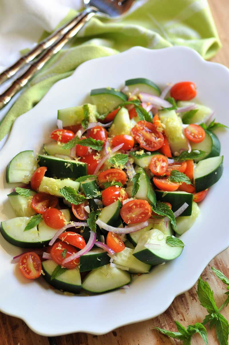 Cucumber, Tomato & Mint Salad on a scalloped edged white platter with a green and white napkin with silver serving utensils next to it