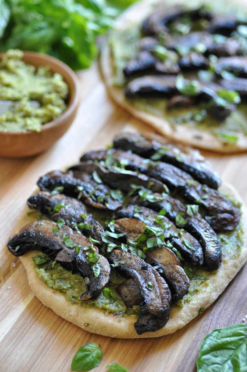 Vegan pesto & Portobello flatbread! on a wooden board with a bowl of pesto and fresh basil leaves on the side