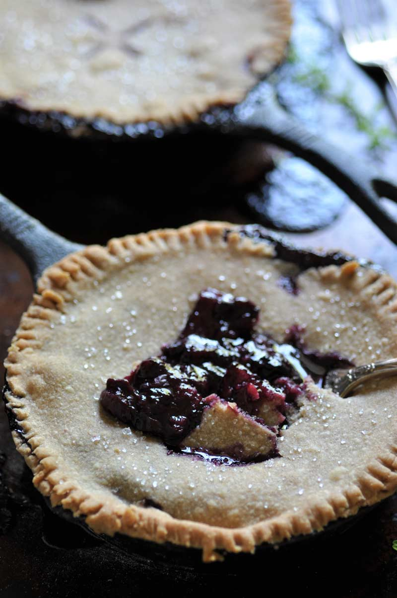 A blueberry pie in an iron skillet with a fork taking a piece out of the center of the pie.