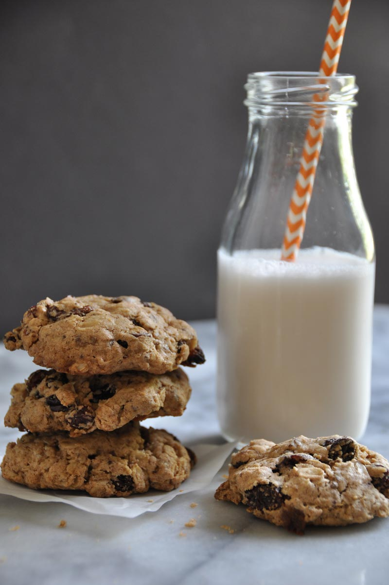 Soft vegan oatmeal raisin cookies stacked next to a bottle of almond milk with an orange and white striped straw in it and a half eaten cookie next to the milk