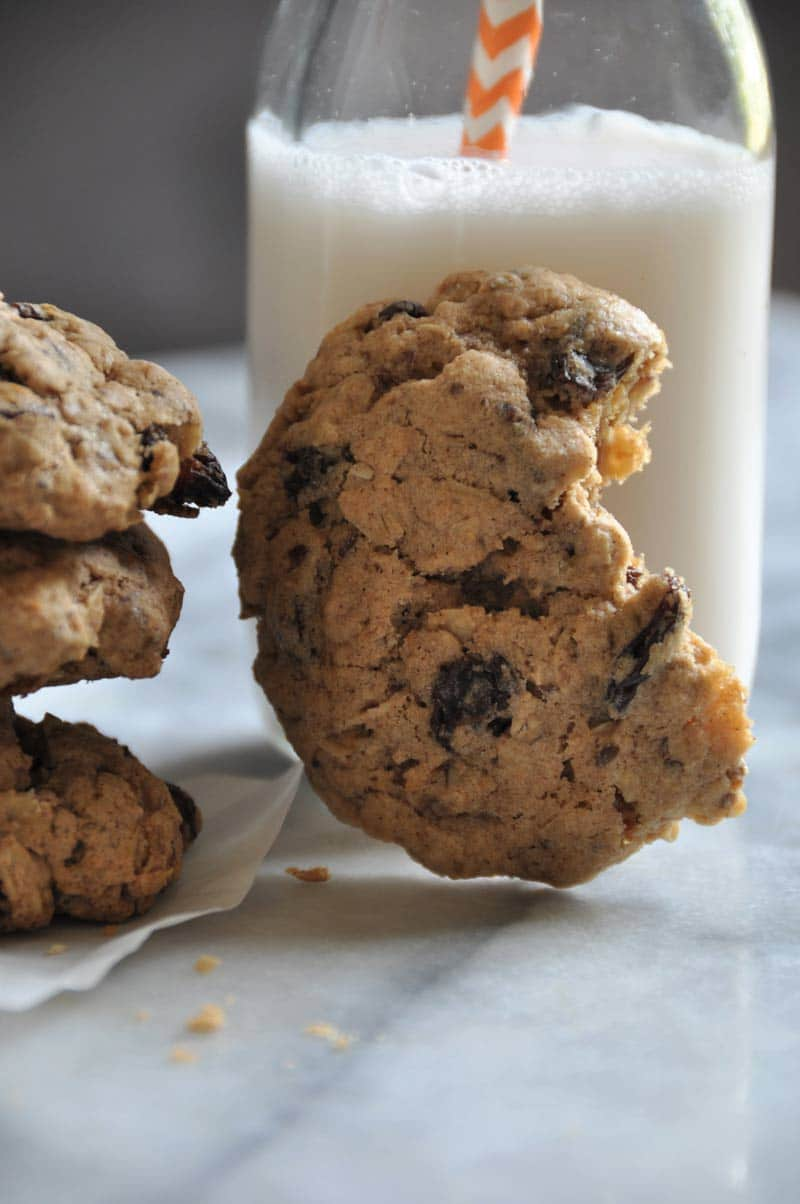 An oatmeal raisin cookie with a bite out of it, leaning on a glass of milk.