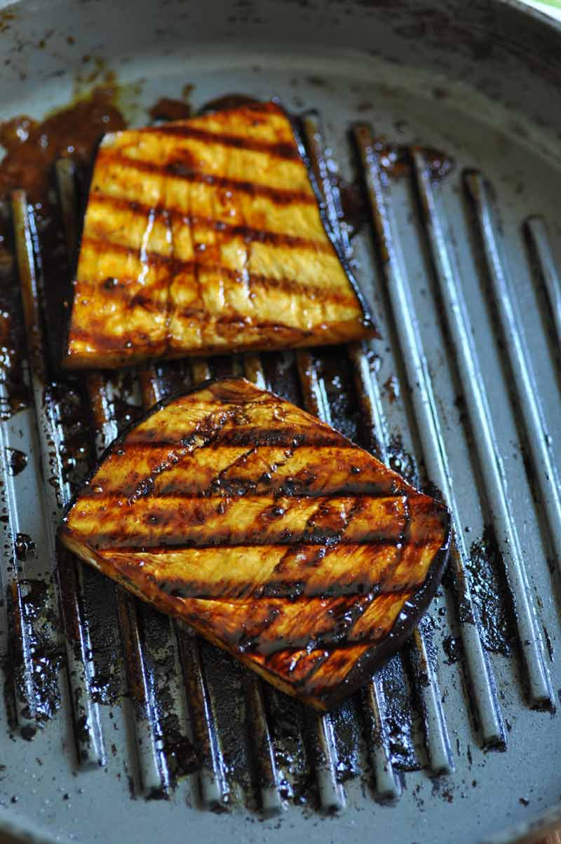 2 slices of marinated grilled eggplant on a grill pan.