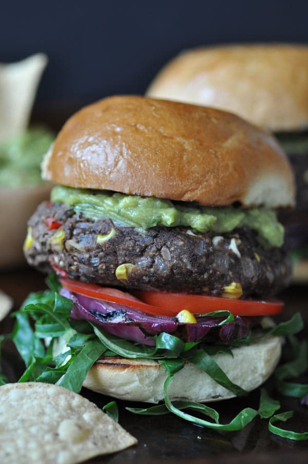 A black bean and veggie burger with corn, tomatoes, lettuce, and guacamole on top.