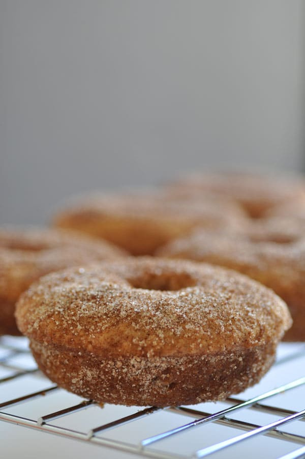 Baked apple cider doughnuts on a wire rack