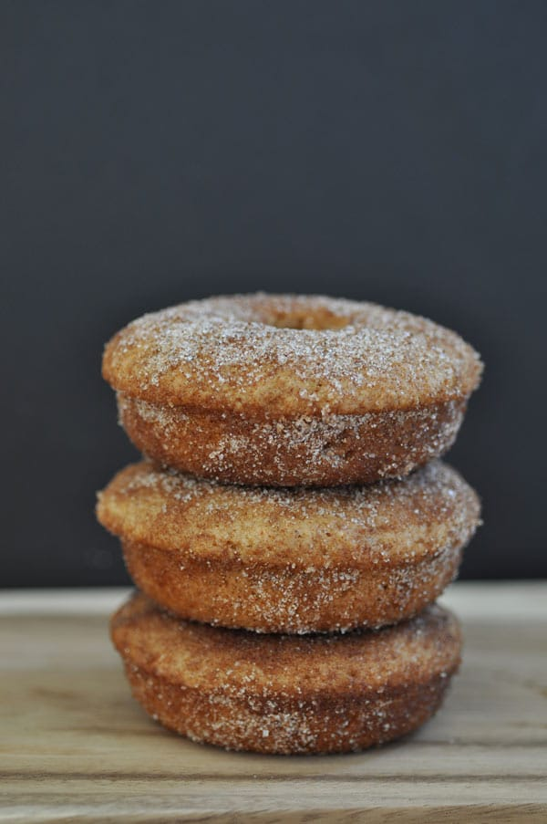 Three baked vegan apple cider doughnuts stacked on a wood board