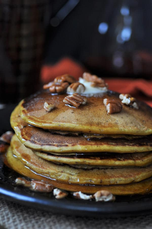 Five vegan pumpkin pancakes with a pat of vegan butter melting on top, with pecans and maple syrup