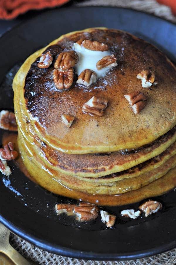An overhead view of a stack of vegan pumpkin pancakes with maple syrup, pecans, and melting butter