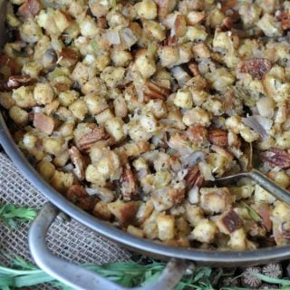 Vegan stuffing in a copper pan with fresh herbs next to the pan