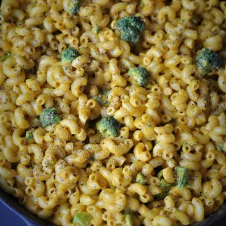 A cast-iron skillet filled with black pepper cheesy mac and brocolli