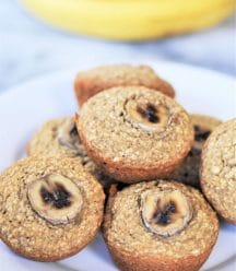 A stack of banana muffins on a white plate with bananas in the background