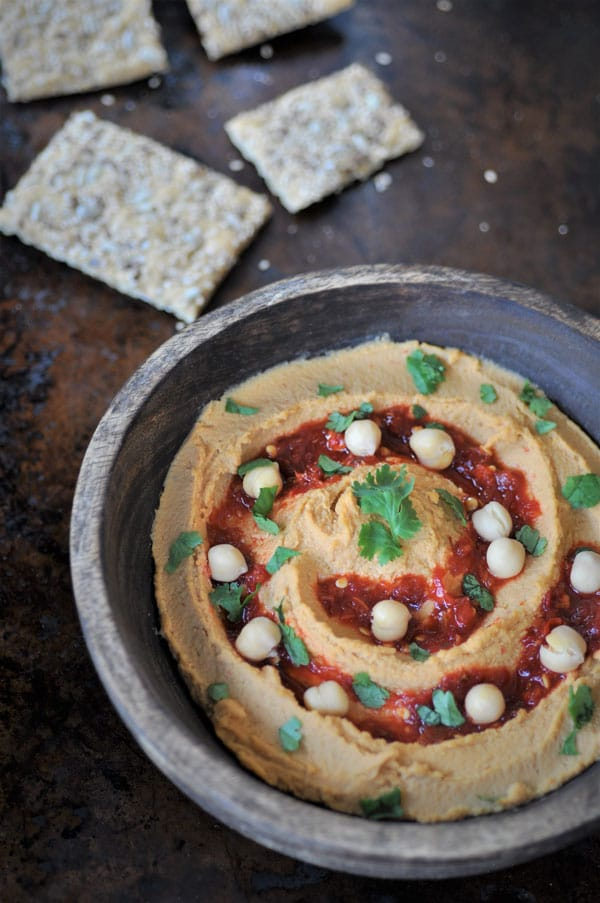 Spicy peanut chili hummus in a wood bowl on a metal table with crackers
