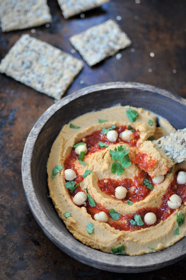 A cracker being dipped into a bowl of spicy peanut chili hummus in a wood bowl