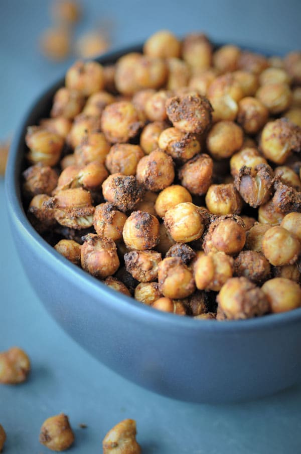 Spicy roasted chickpeas in a black bowl on a black piece of slate with chickpeas spilling over.