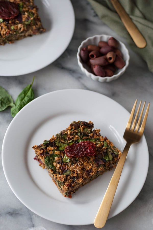 A slice of baked savory oats on a white plate with a gold fork and basil leaves and a dish of kalamata olives in the background