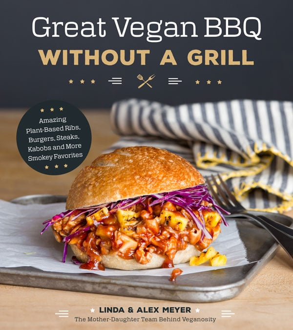 Cover of Great Vegan BBQ Without a Grill with a Shredded jackfruit and grilled pineapple BBQ sandwich with red cabbage on parchment and a silver tray with a silver fork and a blue and white striped napkin