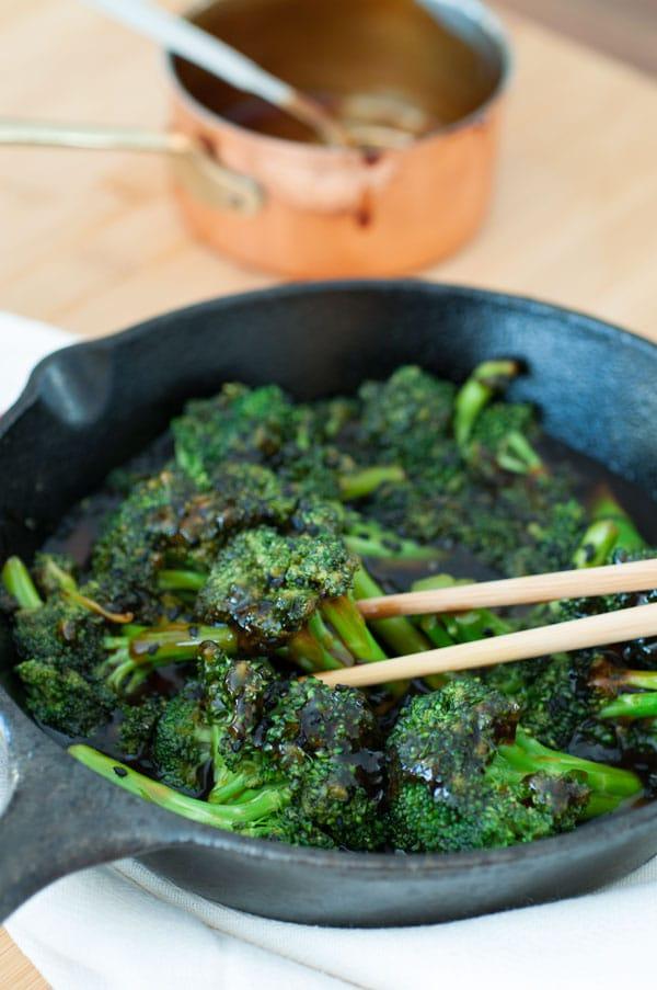 Homemade teriyaki broccoli in an iron skillet with a pair of chopsticks