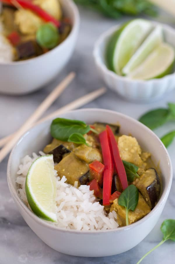 A bowl of green vegetable curry with rice and a slice of lime in a white bowl with chopsticks on the marble table