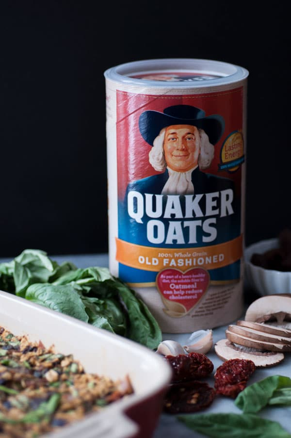 A container of Quaker Old Fashioned Oats with sliced mushrooms, fresh basil, 2 cloves of garlic, and a pan of savory vegan baked oatmeal next to it