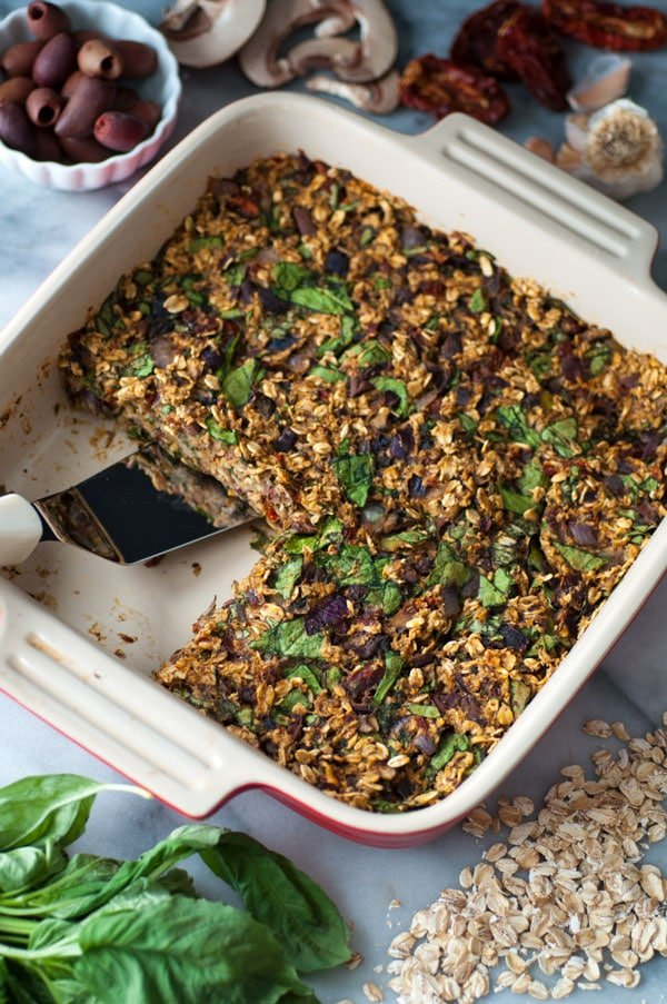A pan of savory vegan baked oatmeal with a piece missing and a spatula in the pan