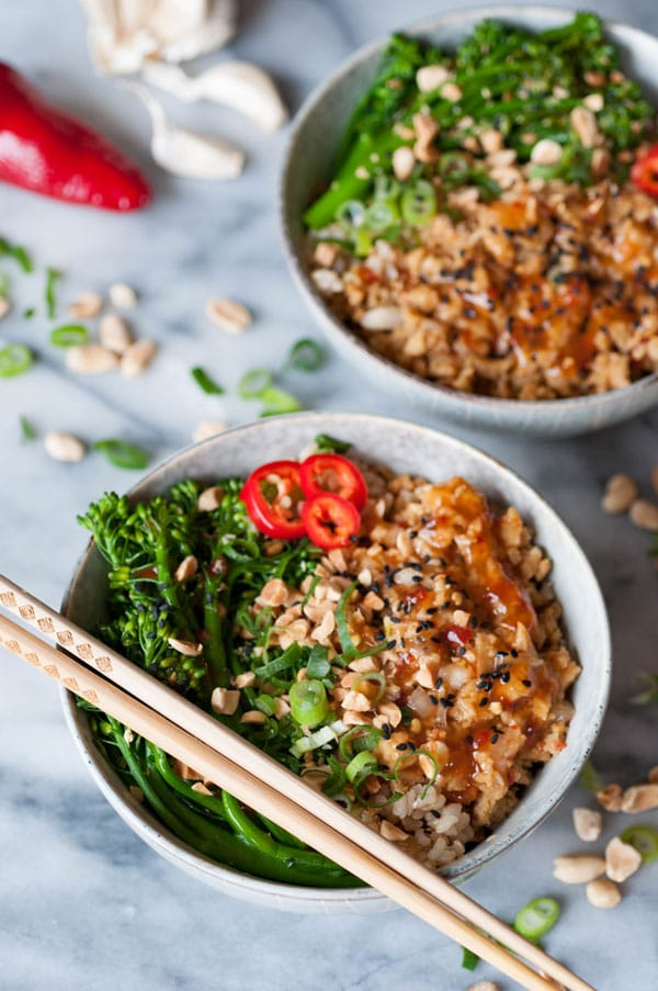 Two bowls of vegan orange chik'n rice bowls with chopsticks and peanuts, chopped green onion, a red pepper, and garlic on a marble counter