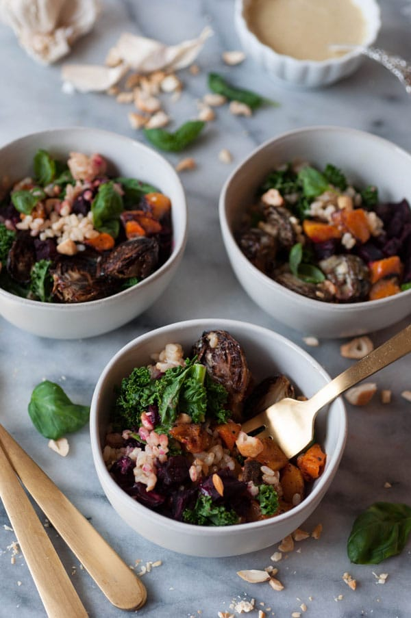 Winter vegetable bowls in three white bowls, one with a gold fork in it.