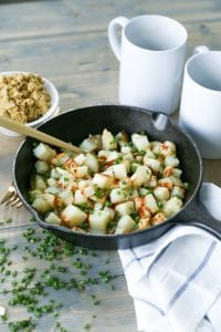 Potatoes in skillet with vegan parmesan, chives, and truffle oil