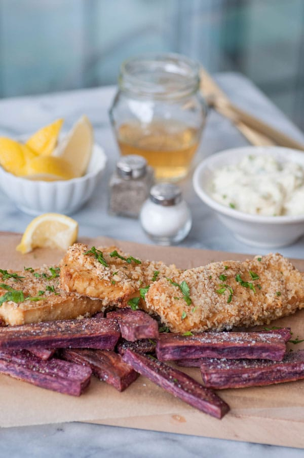 Oven fried vegan fish sticks with purple sweet potato fries on a piece of parchment on a wood board with tarter sauce, lemons, vinegar, and salt and pepper in the background