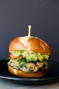 A spinach burger on a bun with avocado and tomato with a toothpick stuck in the center.