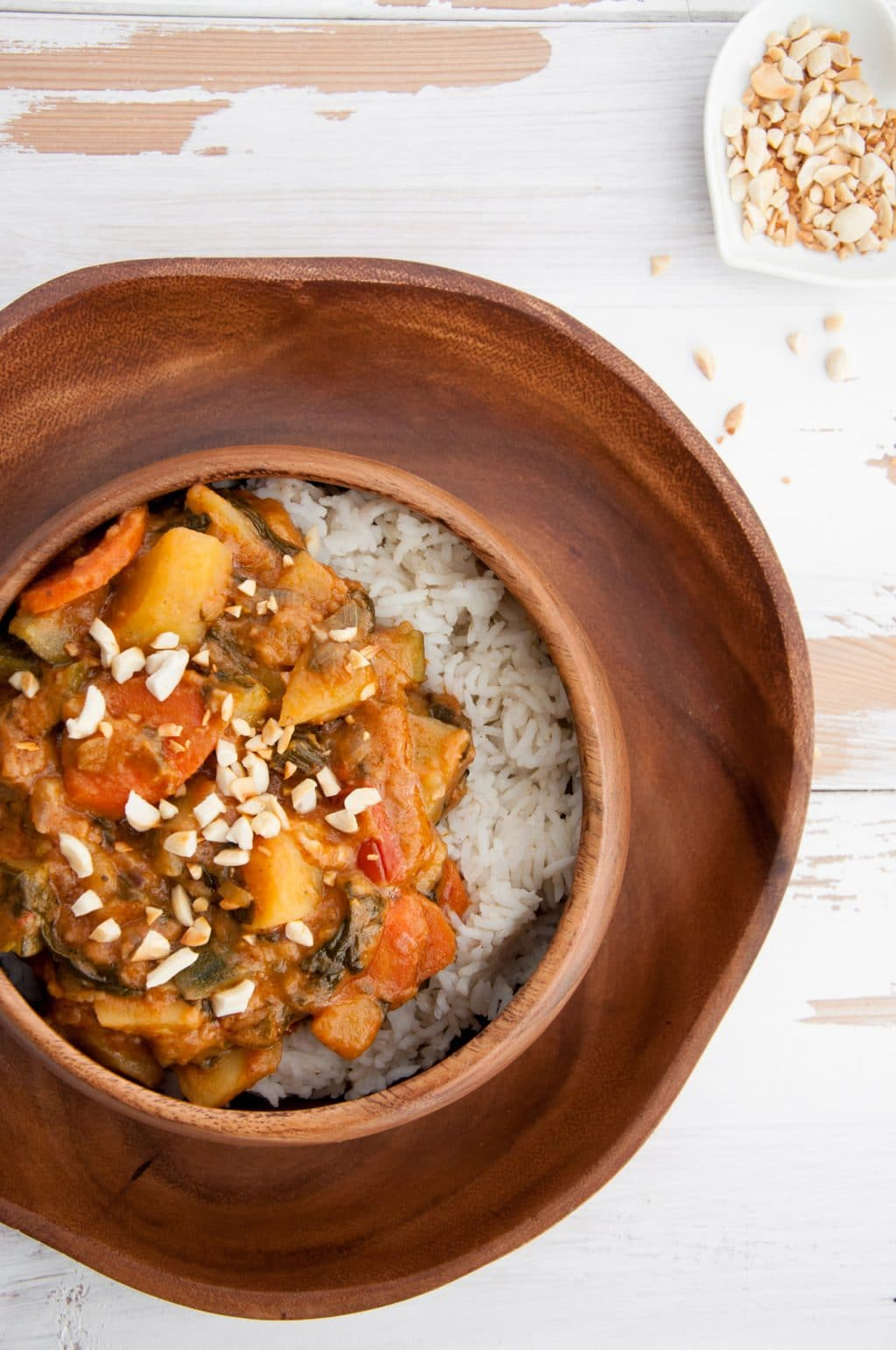 African Peanut Butter Stew in a wood bowl on a wood plate