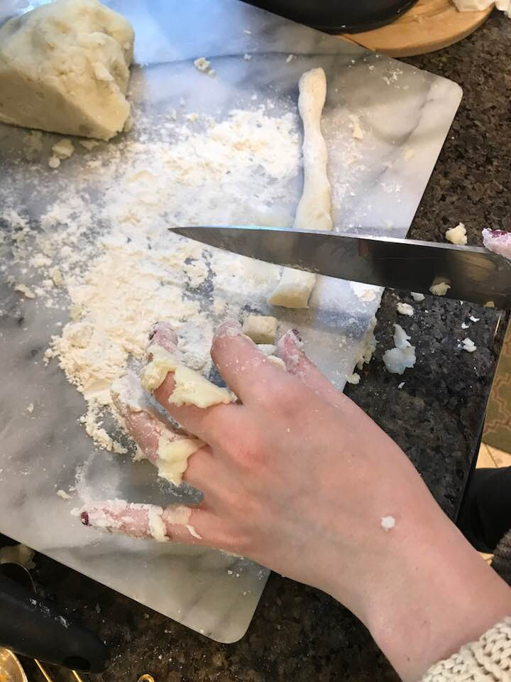 Slicing pieces of rolled out dough to make gnocchi