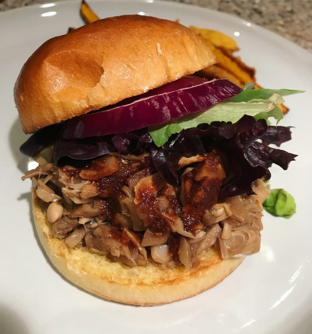 A vegan pulled pork BBQ sandwich on a white plate