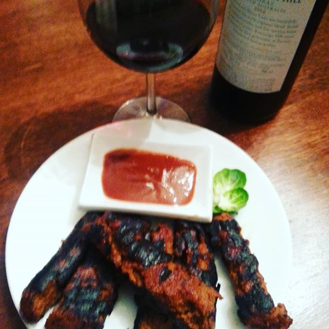 A white plate with vegan BBQ Ribz and a glass of red wine and the bottle next to it.