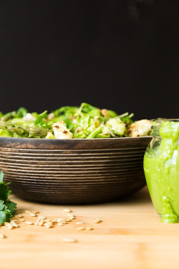 Green Spring Vegetable salad in a wood bowl on a wood surface with sunflower seeds sprinkled in front and part of a glass jar of creamy chimichurri sauce