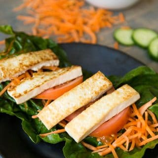 Tofu wrap on black plate with carrots, tomatoes, and cucumber