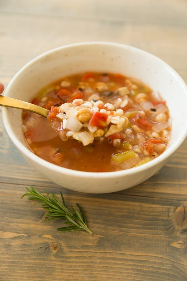 Italian Lemon Rosemary Barley Soup with a gold spoon on a wood cutting board with a piece of rosemary on top