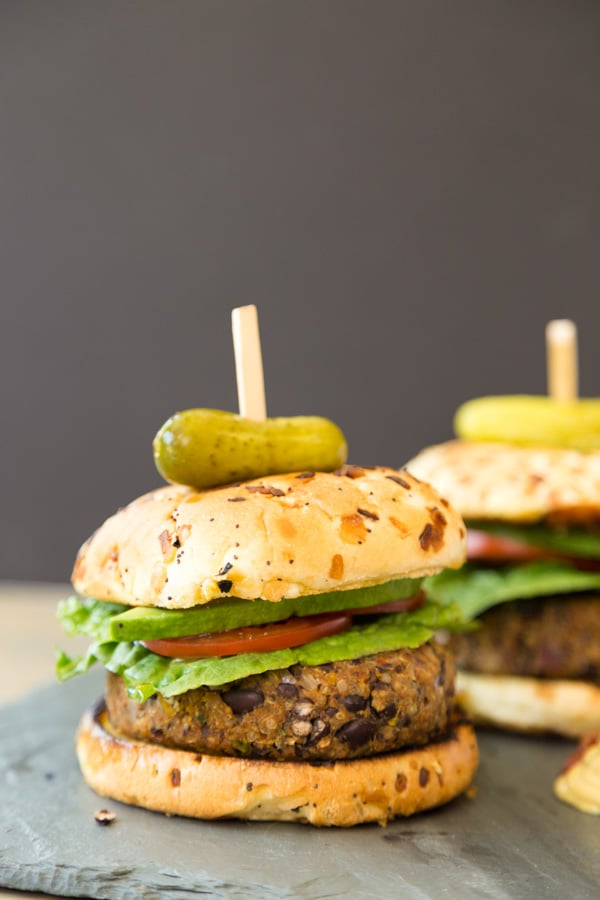 Two black bean burgers with onion buns and a pickle on top on a slate board