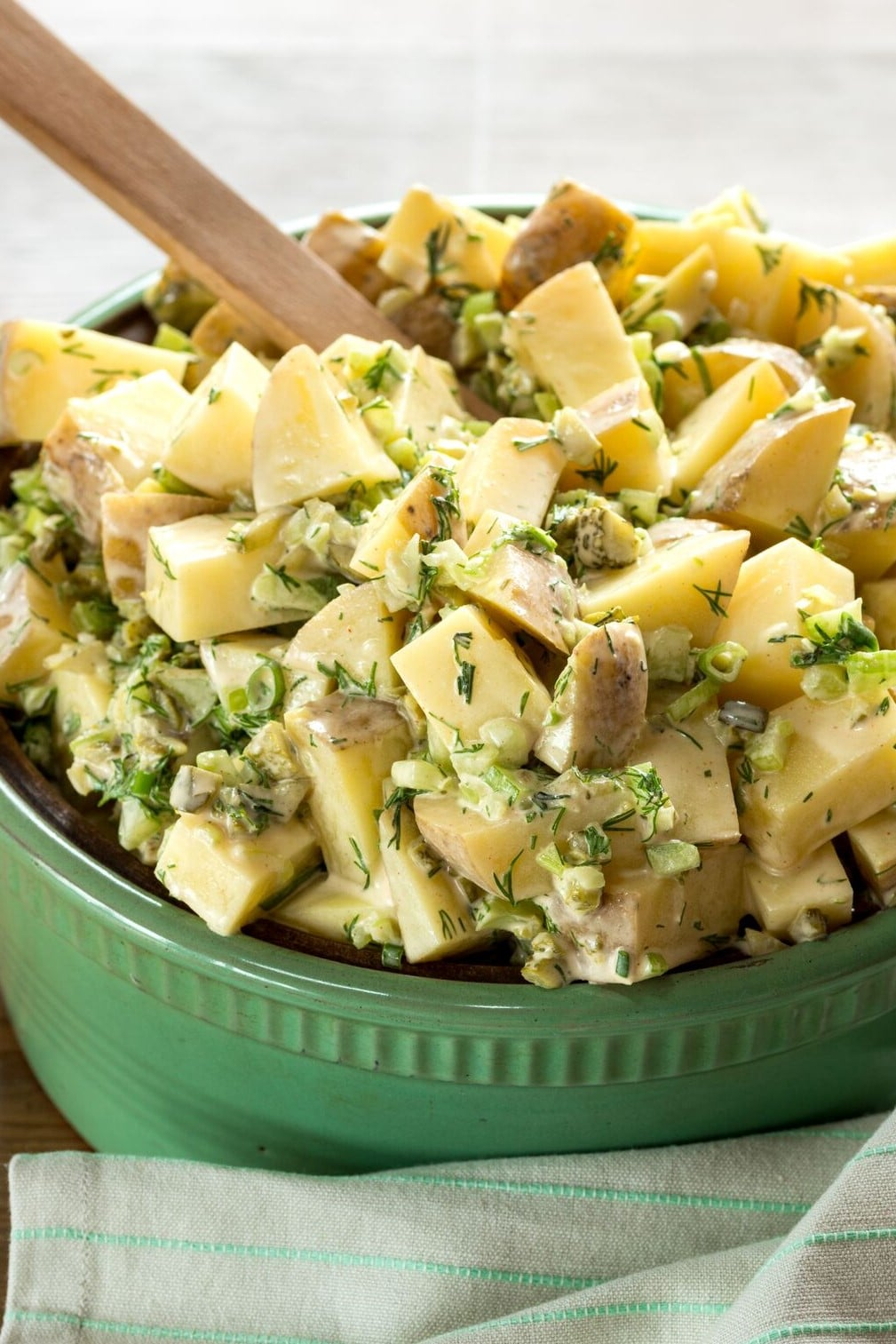 A close up of vegan potato salad in a green bowl with a wooden spoon sticking out of it