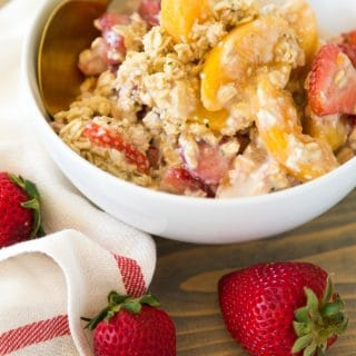 Strawberry Peach Overnight Oats in a white bowl with a gold spoon and strawberries on top of a wood board with a white and red napkin