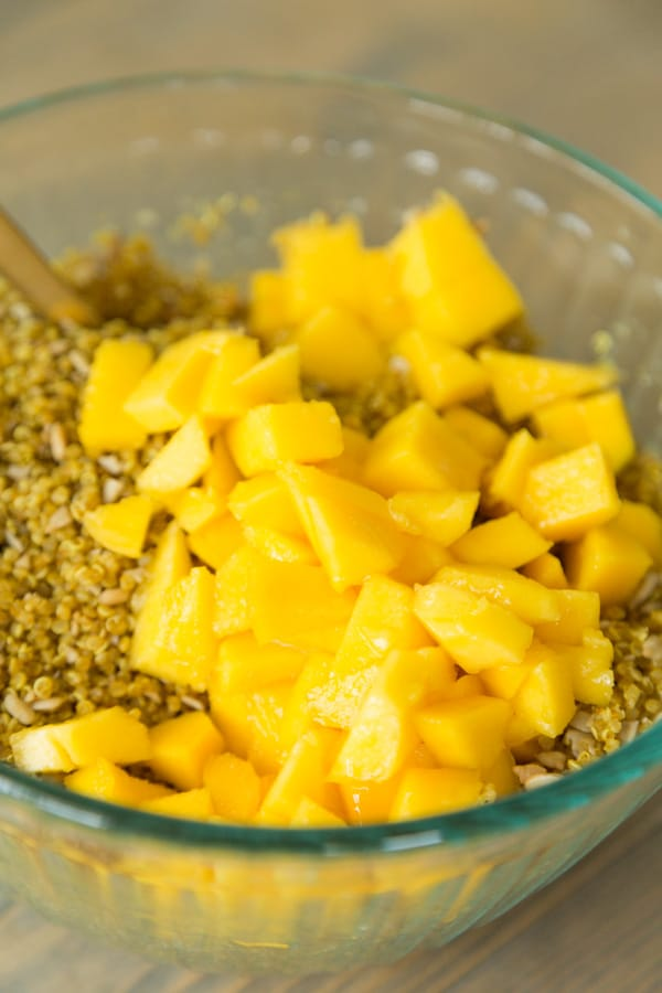 A glass bowl with curried quinoa and mango