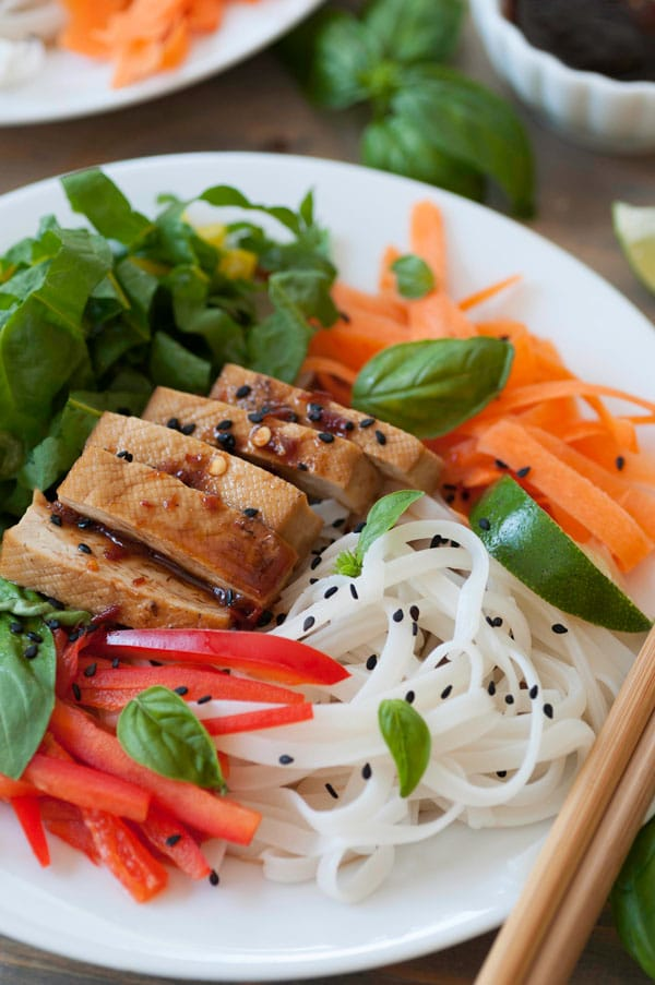 Chilled rice noodles, bell pepper slices, carrots, smoked tofu, chard and basil on a white plate, sprinkled with black sesame seeds