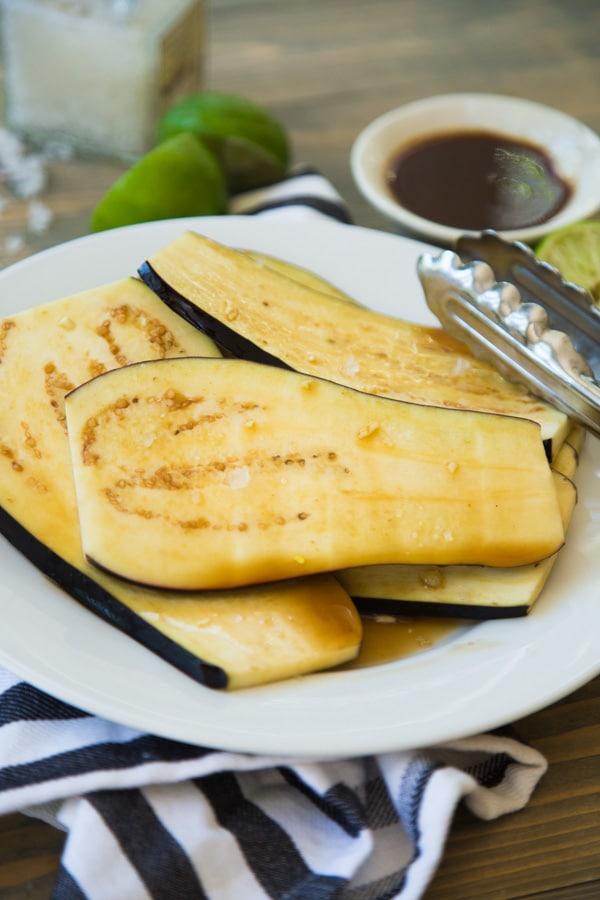 Uncooked teriyaki eggplant in a teriyaki marinade on a white plate