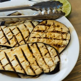 Grilled eggplant with lime zest on a white plate with tongs on a wood board