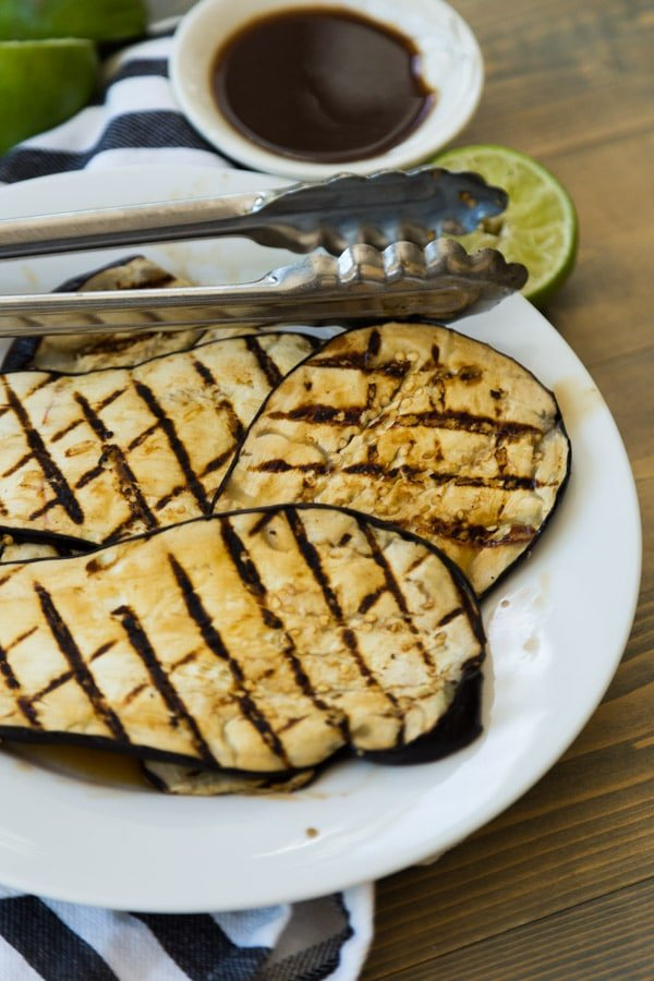 Grilled teriyaki eggplant with lime zest on a white plate with tongs on a wood board