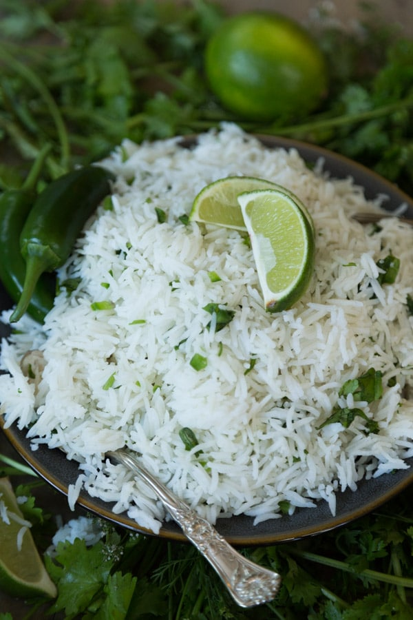 A pile of cilantro lime Mexican Rice on a dark plate with a lime wedge and cilantro on top and a silver fork next to the plate