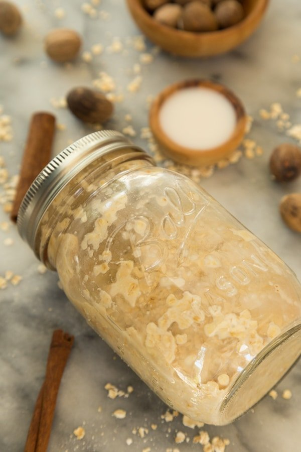 prepared apple overnight oats in a mason jar with a marble background