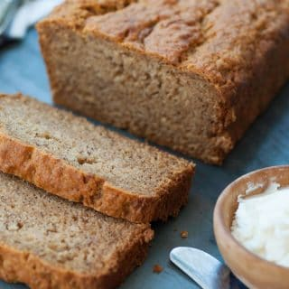 A loaf of vegan banana bread with two slices cut off the end on a slate board with a wood bowl of vegan butter and a butter knife next to the bread