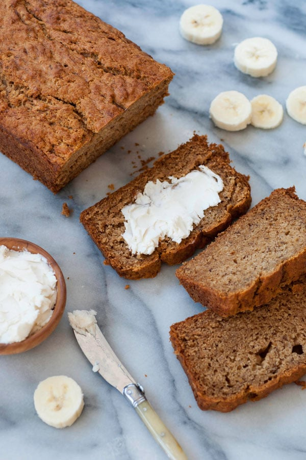 A loaf of vegan banana bread on a marble board with three slices scattered on the board, one of them with a smear of vegan butter and a wood bowl of butter and a butter knife and banana slices scattered around the bread
