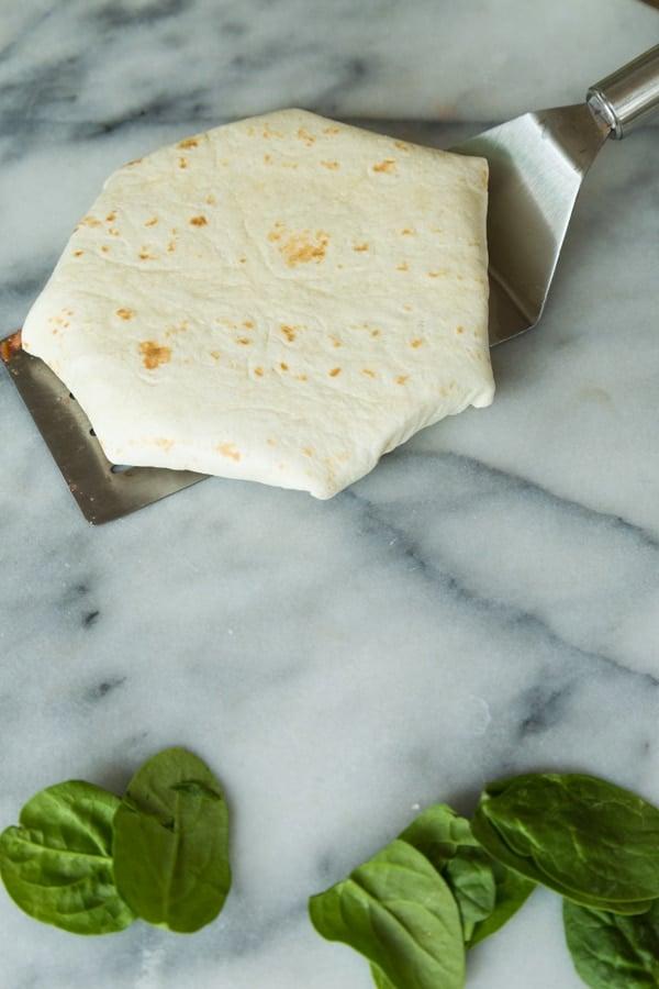 A folded Crunchwrap Supreme on a spatula